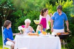 Stor lycklig familj som tycker om bbq-gallret i trädgården Royaltyfria Foton