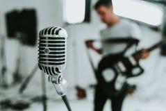 Stor-membran kondensatormikrofon med en musiker som rymmer en elektrisk gitarr i backgroun royaltyfri fotografi