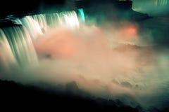 Stor nattsikt av vattenfallet under ljus Arkivfoto