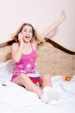 Stor nyheterna: stående av den gulliga roliga unga blonda kvinnan i rosa pyjamas i hållande ögonen på film för säng med popcorn o Arkivbild