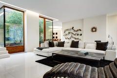Stor och bekväm vardagsrum med en vit soffa Arkivfoto