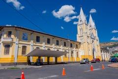 Stor och imponerande kyrka som täckas av en stor himmel Beiga och guling dominerade arkitekturen, säljare på hörnet Arkivfoton