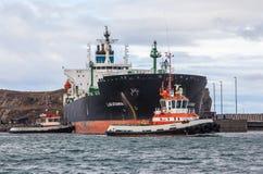 Stor oljetanker med två bogserbåtar Arkivfoto