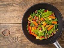 Stor panna som stekas med färgrika grönsaker - peppar, ärtor, gräsplan är Arkivfoton