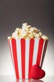 Stor pappers- kopp av popcorn och röd hjärta på en grå färg Royaltyfria Bilder