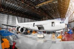 Stor passagerarflygplan i en hangar på tjänste- underhåll arkivbilder