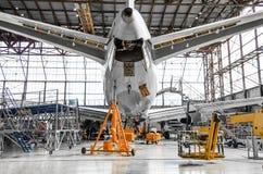 Stor passagerarflygplan på service i en bakre sikt för flyghangar av svansen, på hjälpmaktenheten Royaltyfri Fotografi