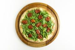 Stor pizza med rucula och torr tomat på vit bakgrund royaltyfri foto