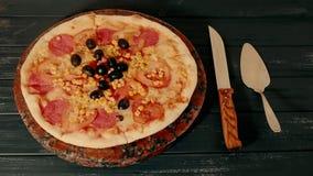 Stor pizza med tomater bredvid en kniv på tabellen Timelapse stock video