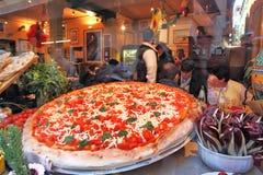 Stor pizza som visas i restaurangfönster i Venedig, Italien. Arkivfoton