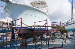 Stor powerboat för Boatyardreparation på kuggar som omges med arbetsscaf arkivfoto