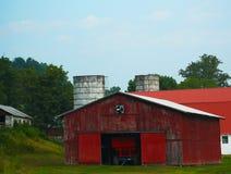 Stor röd ladugård och traktor Arkivbilder