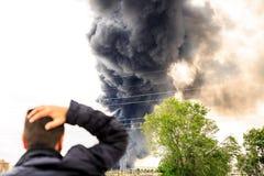 Stor rök från en brand som gör häpen en man Arkivbild