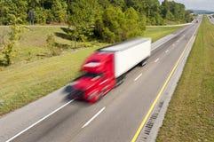 Stor röd lastbil som rusar ner huvudvägen Arkivfoto