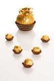 Stor rund chokladgodis som slås in i guld- folie med den stora pilbågen på Arkivfoton