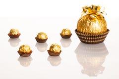 Stor rund chokladgodis som slås in i guld- folie med den stora pilbågen på Arkivbild