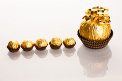 Stor rund chokladgodis som slås in i guld- folie med den stora pilbågen på Fotografering för Bildbyråer