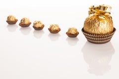 Stor rund chokladgodis som slås in i guld- folie med den stora pilbågen på Arkivbilder