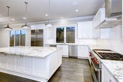 Stor rymlig kökdesign med vita köksskåp royaltyfria foton