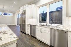 Stor rymlig kökdesign med vita köksskåp fotografering för bildbyråer