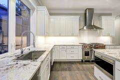 Stor rymlig kökdesign med vita köksskåp royaltyfri foto