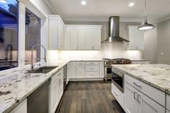 Stor rymlig kökdesign med vita köksskåp royaltyfri bild