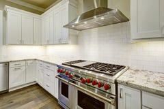 Stor rymlig kökdesign med vita köksskåp royaltyfri fotografi