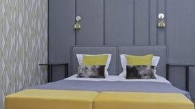 Stor säng i ett modernt lyxigt lägenhetsovrum, i grå färger Royaltyfria Foton