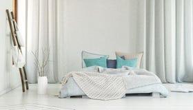 Stor säng i rum med långa vita gardiner Royaltyfria Bilder