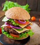 Stor saftig hamburgare med grönsaker på en träbakgrund Arkivbilder
