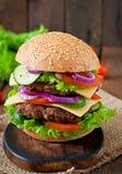 Stor saftig hamburgare med grönsaker på en träbakgrund Royaltyfri Bild