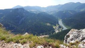 Stor sikt av en sjö som omges av skogar och bergmaxima Fotografering för Bildbyråer