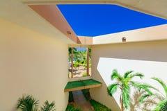 Stor sikt av hotellbyggnadsarkitektur inom väggar med fönstret som leder till den tropiska trädgården Royaltyfria Bilder