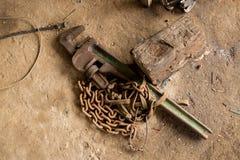 Stor skruvnyckel för justerbar skiftnyckel med Rusty Old Chain och en övergiven konkret jordning för inloggning royaltyfri fotografi