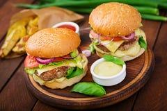 Stor smörgås - hamburgare med den saftiga nötkötthamburgaren, ost, tomaten och den röda löken Royaltyfri Bild