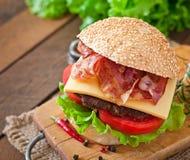 Stor smörgås - hamburgarehamburgare med nötkött, ost, tomat Arkivbild