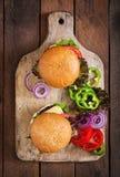 Stor smörgås - hamburgarehamburgare med nötkött, ost, tomaten och tartarsås Arkivbild