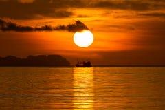 Stor sol och kontur av fiskebåten Arkivfoto