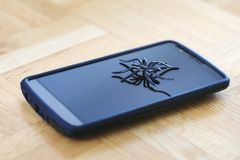Stor spindelleksak som poserar på yttersida av mobiltelefonen arkivbilder