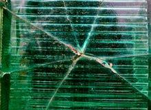 Stor spricka i mitt av den gröna glasväggtexturen, bakgrund royaltyfri bild