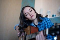 Stor stående av en kvinna som är förlovad, i att undervisa den akustiska gitarren på sängen i sovrummet fotografering för bildbyråer