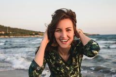 Stor stående av en ung kvinna på stranden på den röda solnedgången, selfie, leende, gyckel, semester arkivfoton