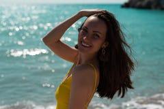 Stor stående i det hårda ljuset av den ljusa solen av en ung kvinna på havet i en gul baddräkt, verkliga livet royaltyfri fotografi