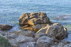 Stor stenig klippa för havskust med blå havsbakgrund Fotografering för Bildbyråer