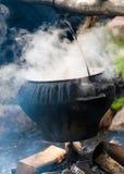 Stor svart matlagningkruka på brand utomhus arkivbild