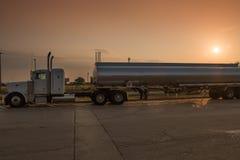 Stor tankfartyg för släp för rigglastbiltraktor på gryning med solen i bakgrund arkivbilder