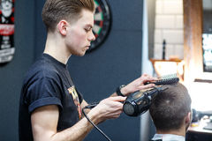Stor tid på frisersalongen Det gladlynta barnet uppsökte mannen som får frisyr av frisören, medan sitta i stol på frisersalongen Arkivbild
