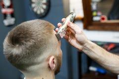 Stor tid på frisersalongen Det gladlynta barnet uppsökte mannen som får frisyr av frisören, medan sitta i stol på frisersalongen Fotografering för Bildbyråer