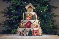 Stor tiered jul bakar ihop dekorerat med pepparkakakakor och ett hus överst Träd och girlander i bakgrunden arkivfoto