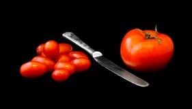Stor tomat, hög av små tomater och kniv dem emellan Royaltyfri Foto
